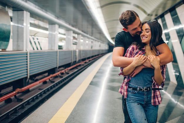 若い男と女は地下を使用します。地下鉄のカップル。彼は彼女の後ろに立って抱擁します。キスシーン。陽気な若い女性の笑顔。ラブストーリー。