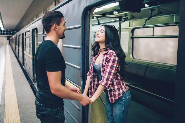 若い男と女は地下を使用します。地下鉄のカップル。若いブルネットは地下車両と笑顔で立ちます。彼女は男の手を握る。男はプラットフォームに立っています。恋愛。陽気な。