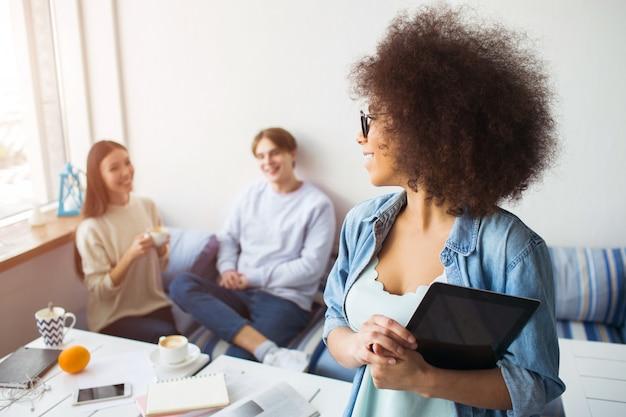 Афро американская девушка держит планшет в ее руках и смотрит на ее друзей, которые сидят на диване, улыбается и смотрит на нее.