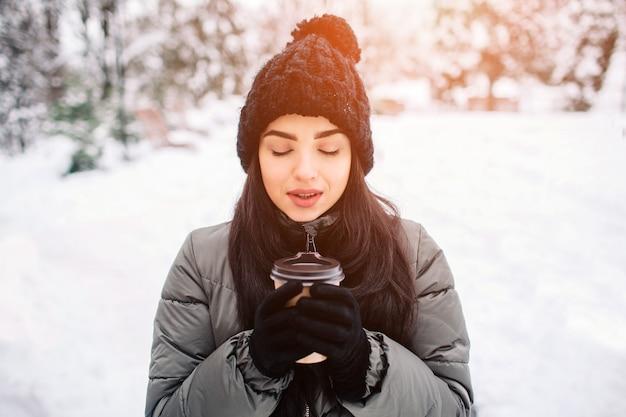 熱いお茶や雪の降る冬のコーヒーのカップを持つ幸せな若い女性は、自然の中を歩きます。冬の霜の概念。
