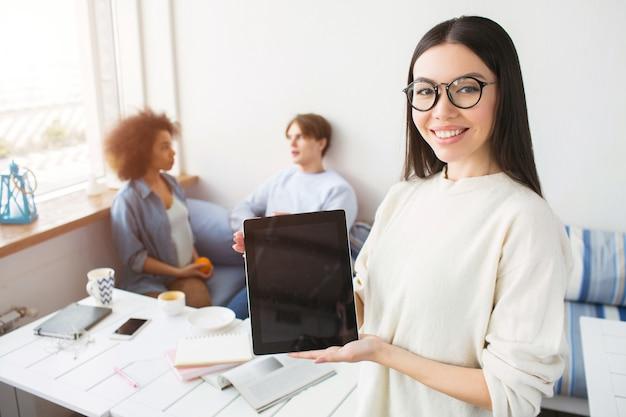 Азиатская девушка держит планшет в ее руках. она это демонстрирует. девушка носит очки и улыбается. ее друзья сидят на диване и разговаривают друг с другом.
