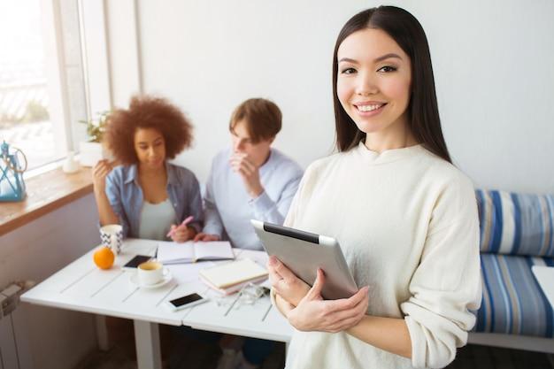 Красивая девушка в белом свитере стоит и позирует. она держит планшет в руках и улыбается. ее друзья сидят позади нее и учатся.