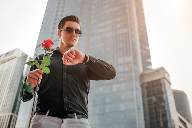 Молодой красавец стоять перед небоскреб и смотреть на часы. он держит в руке красную розу.