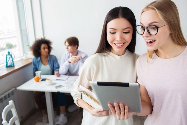 Две умные девушки стоят и смотрят на планшете. блондинка носит очки. ее друзья держат ноутбук. за ними сидят их друзья и учатся.