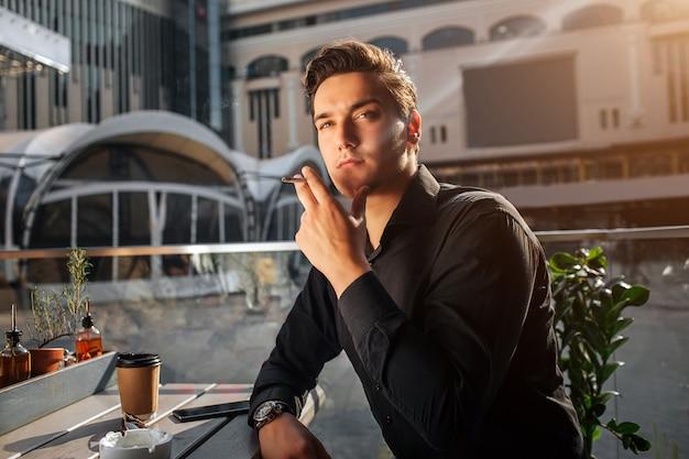 テーブルに座って喫煙の若い男の写真。彼は右を見上げます。男はテーブルにもたれます。彼は外に座っています。太陽が輝いている。