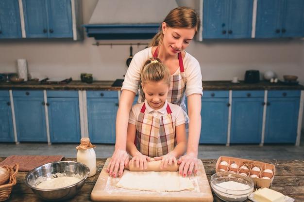 自家製ケーキを調理します。幸せな愛情のある家族が一緒にベーカリーを準備しています。母と子の娘の女の子は、クッキーを調理し、キッチンで楽しんでいます。生地を転がします。