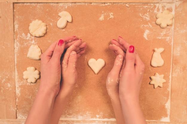 ハート形の上面に生地を保持している女性の手。暗い木製のテーブルに食材を焼きます。