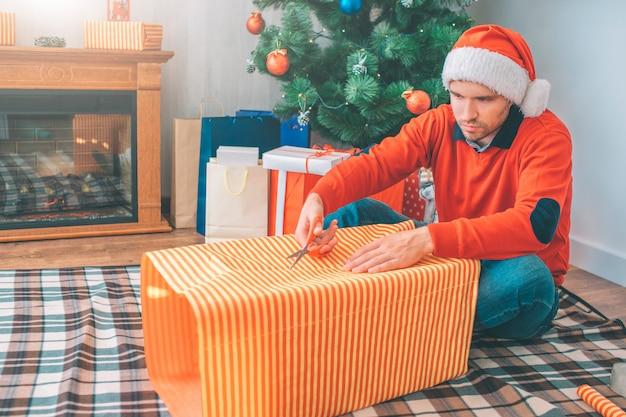 深刻な若い男は毛布の上に座って、はさみで紙を切る