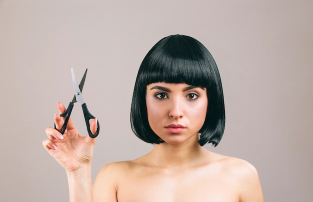 Молодая женщина с черными волосами позирует. глядя прямо. держа ножницы в руке. серьезная брюнетка с стрижкой боба.