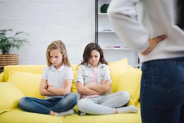 Грустные и расстроенные подростки сидят на диване в комнате и смотрят вниз. они держат руки и ноги скрещенными. молодая женщина стоит перед ними. она держится за руки на бедрах.