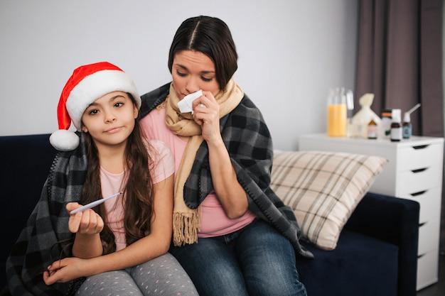 Маленькая девочка сидит на диване со своей больной мамой