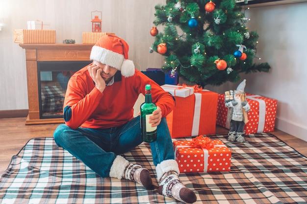 床に毛布の上に座って、ボトルを見て退屈して酔っている若い男