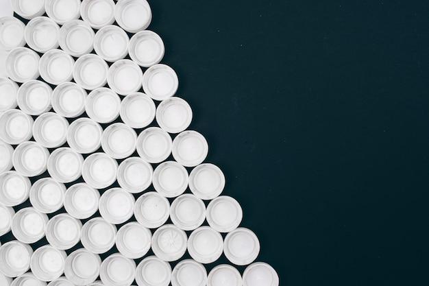 Концепция пластического загрязнения. белые пластиковые крышки на темном фоне расположены по диагонали. одноразовый пластик. откажитесь от одноразовой пластиковой концепции. сохранить экологию