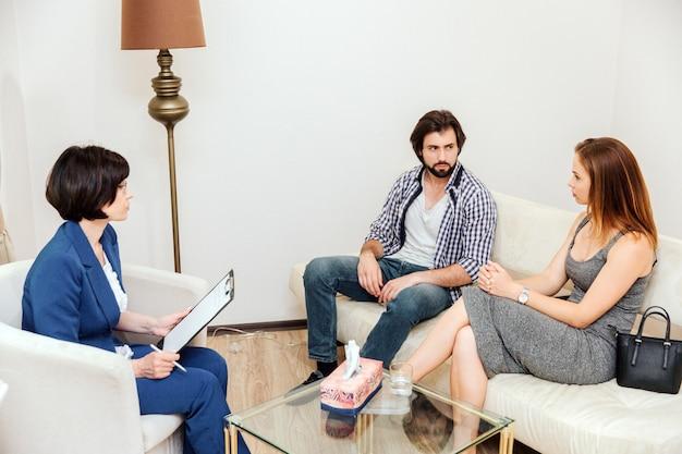 ソファーに一緒に座って、非常に真剣に見ているカップルの写真。医者はそれらを見て、紙のタブレットを手に持っています。
