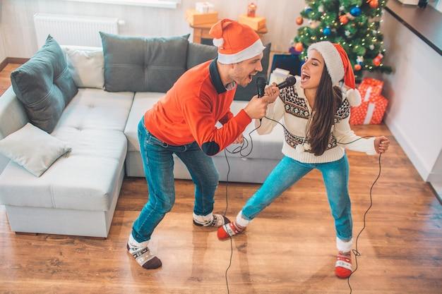 Эмоциональная пара стоит и поет вместе с помощью микрофона