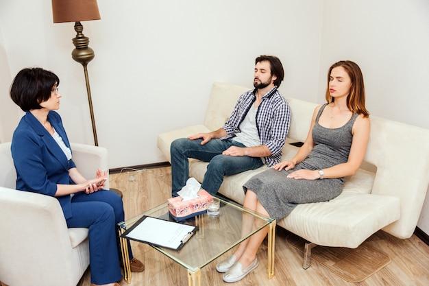 Спокойные и мирные люди сидят вместе с закрытыми глазами. они работают с психологом. доктор смотрит на молодых пар и разговаривает с ними.