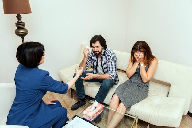 Расстроенная пара сидит вместе и плачет. они в отчаянии. доктор сидит перед ними и дает чашку воды.