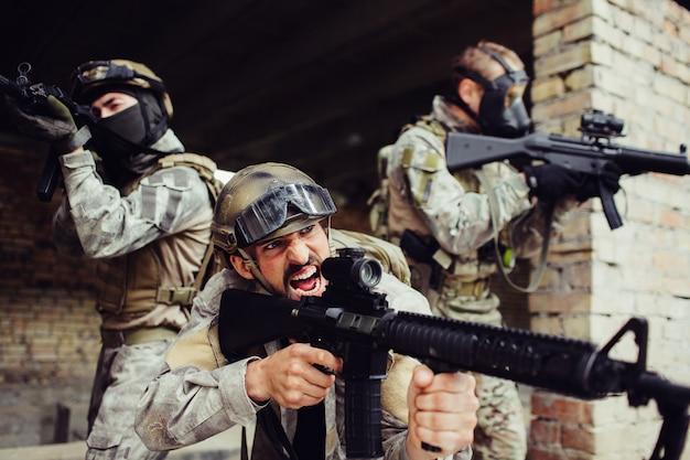 感情的なフロントマンは、兵士たちと外に立って叫んでいます。それらはすべて黒いライフルを持っています。彼らは危険です。男は戦う準備ができています。
