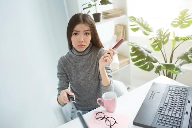 Грустный и разочарованный блогер сидит в светлой комнате и смотрит в камеру