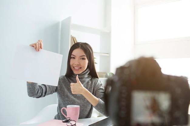 Привлекательная женщина, сидя перед камерой и показывая чистый лист бумаги