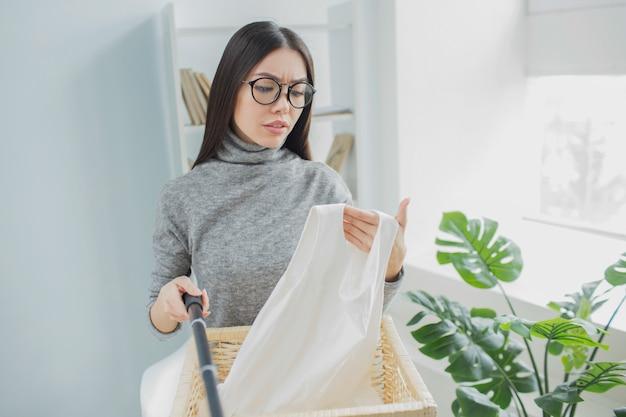 Женщина держит камеру на селфи палку и держит кусок белой одежды