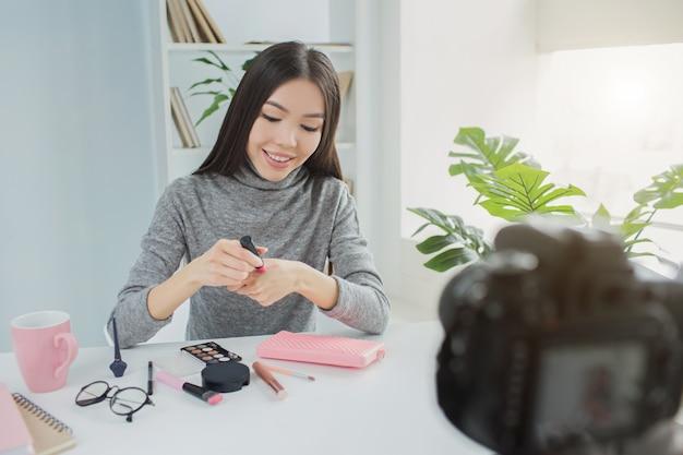 美しい女性がテーブルに座って、今月の美容製品についてのビデオを作成しています