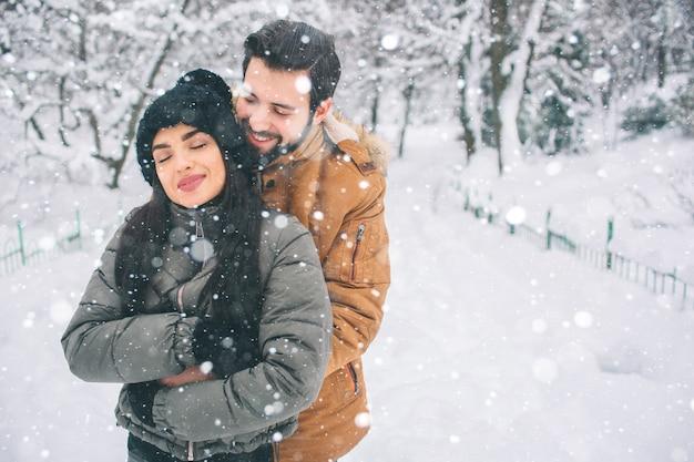 Счастливая молодая пара в зимний период. семья на открытом воздухе. мужчина и женщина смотрит вверх и смеется. любовь, веселье, сезон и люди - гуляют в зимнем парке. идет снег, они обнимаются