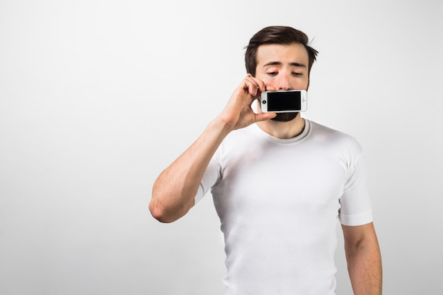 Интересная фотография парня, стоящего у большой белой стены и закрывающего рот телефоном в правой руке. он выглядит обеспокоенным и обеспокоенным. изолированные на белой стене.