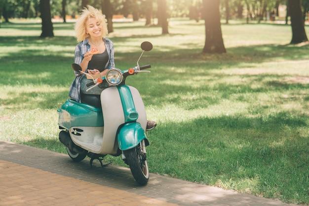 モトスクーターや原付けで食べる女の子。モトスクーターや原付けで食べる女の子。ボックスで熱いピザを保持している幸せな若い女性。女子学生には時間がありません、彼は外出先で食べるつもりです
