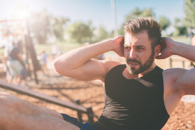 Мускулистый мужчина, упражнения, делать сидеть упражнения. спортсмен с шестью пакетами, белый мужчина, открытый тренировки. спорт и здоровый образ жизни. бородатый черноволосый парень делает хрустит на открытом воздухе.