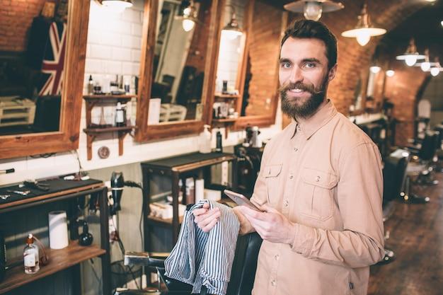 Счастливый и веселый парень стоит в парикмахерской и смотрит в камеру. он улыбается человек держит прикрытие для плеч клиента.