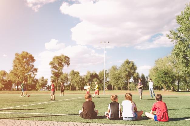 子供サッカーチームの試合。子供向けサッカーゲーム。ピッチの上に座って若いサッカー選手。青と赤のサッカージャージースポーツウェアの小さな子供たちは、アウトで待っています。