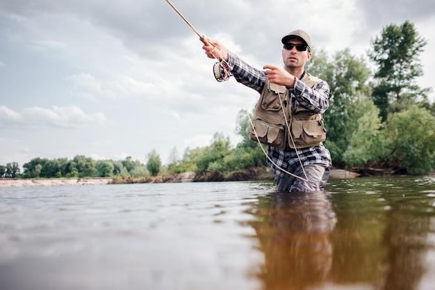Рыбак в действии. парень бросает в воду ложку мухи и держит ее в руке. он смотрит прямо вперед. человек носит специальную защитную одежду.