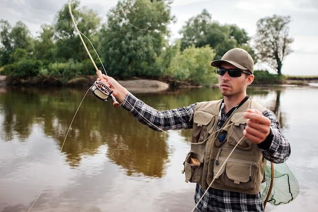 Серьезный и сосредоточенный человек стоит в воде и ловит нахлыстом с катушкой под ним в одной руке и частью ложки в другой. также у человека есть рыболовная сеть на спине. он рыбачит.