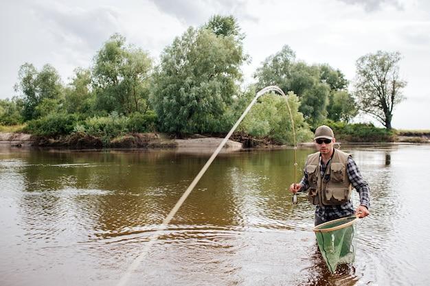 Рыбак стоит на мелководье и смотрит прямо вперед. у него нахлыстом в руках. ложка показана на камеру.