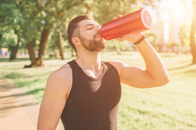 男は鉄の瓶と飲料水を保持しています。屋外トレーニング後休んで若いハンサムな整形式のスポーティな男。男性フィットネスモデルトレーニングトレーニング