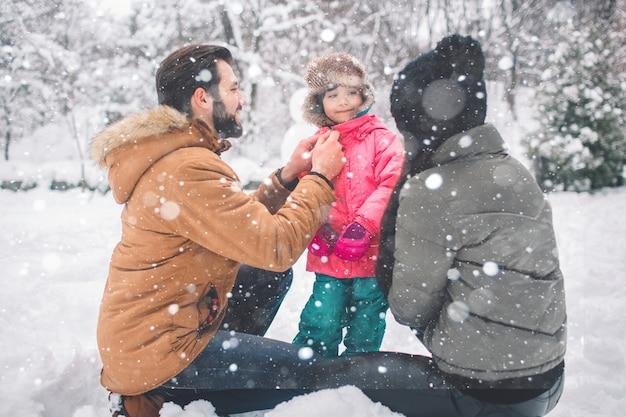 Родительство, мода, сезон и люди концепции - счастливая семья с ребенком в зимней одежде на открытом воздухе