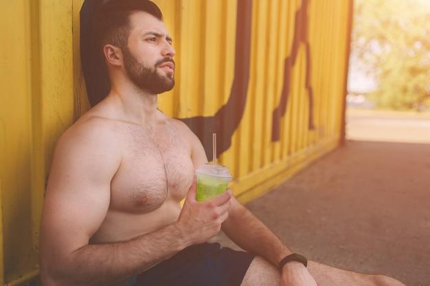 ハンサムな若い筋肉男は緑のデトックススムージーカップを飲みます。トレーニング後の運動青年の写真。