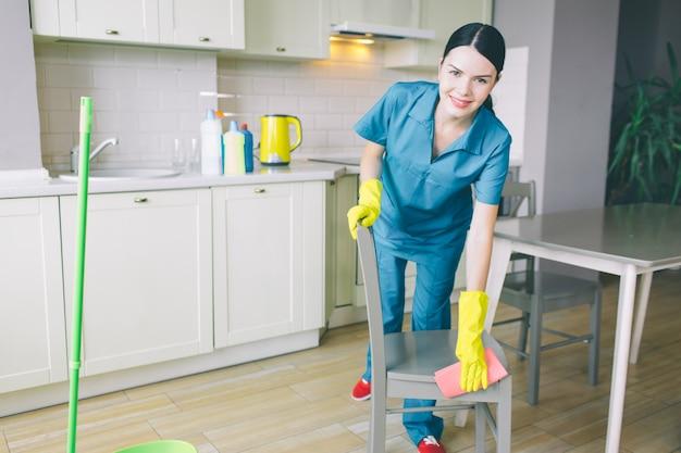 肯定的で素敵なブルネットの女性は、キッチンで働いています