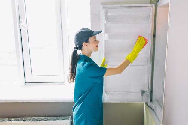 ウィンドウでキッチンで働く気分が良い女性