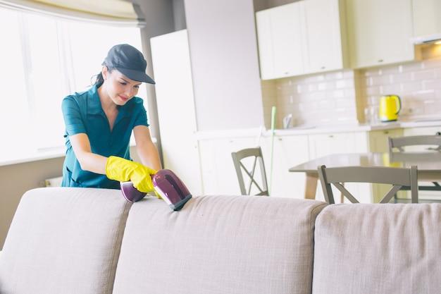 Женщина чистит край дивана