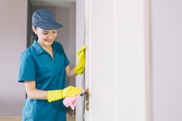 幸せで陽気な女性が立ち、白いドアを保持