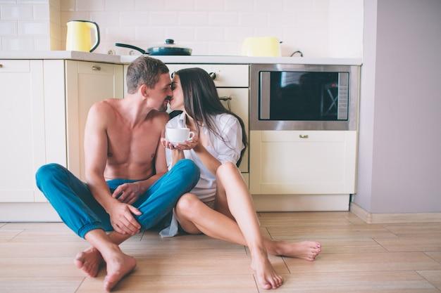 男と女の台所の床に座ってキス