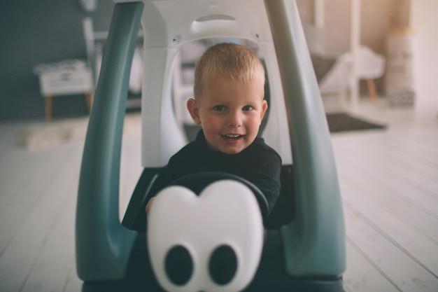 子供は床に横たわっています。少年は午前中自宅でおもちゃの車で家で遊んでいます。寝室でのカジュアルなライフスタイル。