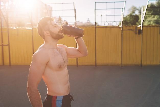 トレーニング後の運動青年の写真。ハンサムな若い筋肉男はタンパク質を飲みます。ブレンダーからスポーツ栄養シェイクを飲む魅力的な運動上半身裸のスポーツ選手。