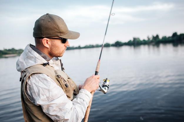 Человек в кепке, солнцезащитных очках и жилете, стоящем в мелком и смотрящем на муху. он использует неинерционную катушку. парень сосредоточен.