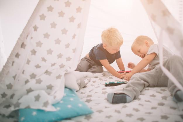 子供の兄弟が床に横たわっています。朝、男の子は家でおもちゃの車で遊んでいます。寝室でのカジュアルなライフスタイル。