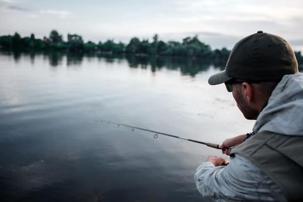 Вырезать вид человека, стоящего спиной к камере. он спокоен и сосредоточен. парень смотрит на воду. он держит муху обеими руками. на улице вечер.