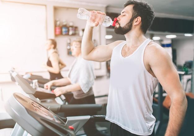 トレッドミルで実行され、ジムで水を飲むスポーツウェアの若い男。トレーニング中に筋肉のひげを生やしたアスリート。屋内フィットネスセンターで若い運動女性モデル列車のクローズアップ。