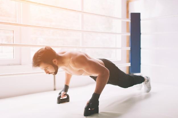 ボクシングリングで腕立て伏せを行う裸の胴体を持つ集中ボクサーの側面図。